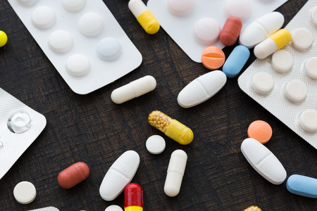 Colorful pills and blusters sitting on dark table surface viewed in closeup from high angle
