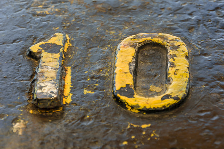 rusts: A number ten yellow on a bollard in the dock
