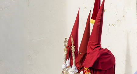 Three penitents waiting for the entrance to the temple on Holy Friday in Huelva, Spain Stock Photo