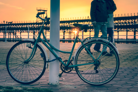 A couple strolls next to a vintage bicycle near the Rio Tinto pier in Huelva Spain as the sun goes down Stock Photo