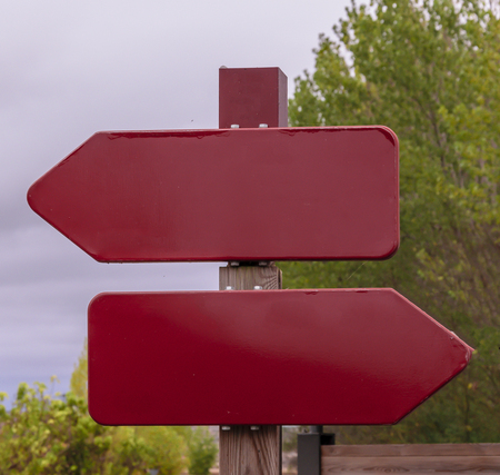 Two red burgundy signs without text pointing opposite directions
