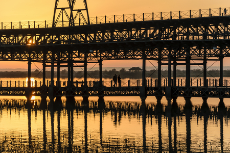 Three people walk on the dock of Rio Tinto at sunset, Huelva, Andalusia, Spain