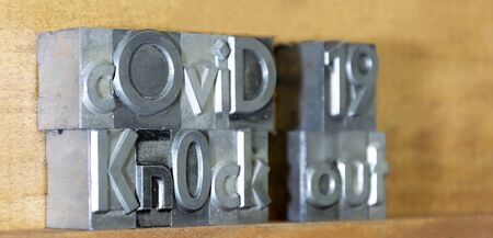 Covid 19 knock out created with movable type printing on a shelf celebrating victory over pandemic