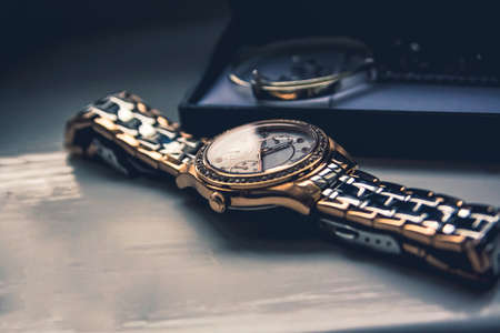 golden watch laying flat on a wooden board