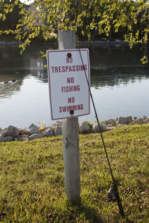 A No Fishing sign with a fishing pole leaning against it. Stok Fotoğraf