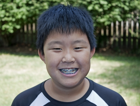 Young boy smiling and showing his braces