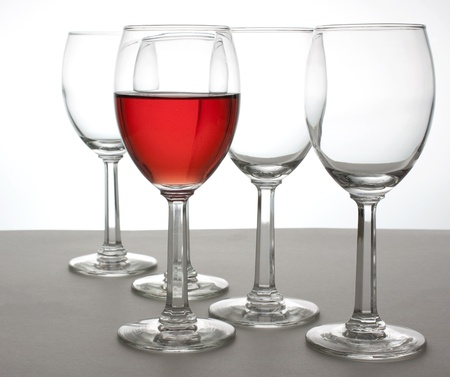A glass of White Zinfandel and four empty wine glasses