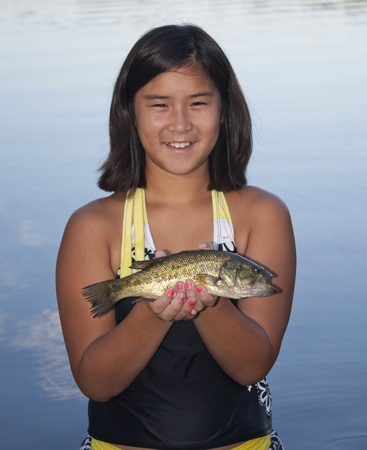 A young girl holding a largemouth bass