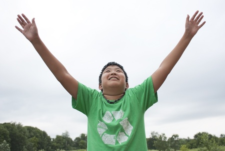Young Boy wearing a recycle shirt and reaching for the skies