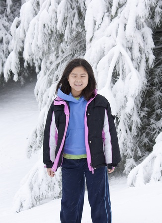 Young Korean girl standing in front of a snow covered tree Stok Fotoğraf