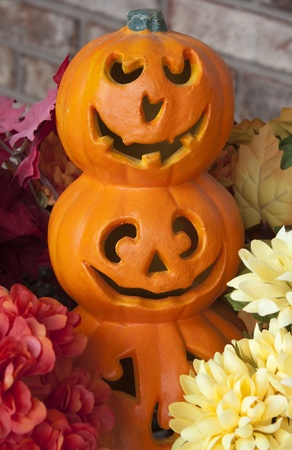 A decoration of 3 stacked jack-o-lanterns surrounded by flowers