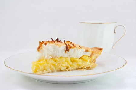 A slice of coconut cream pie with a white background
