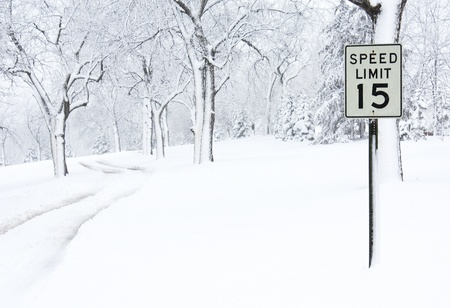 A speed limit sign on a snow covered road