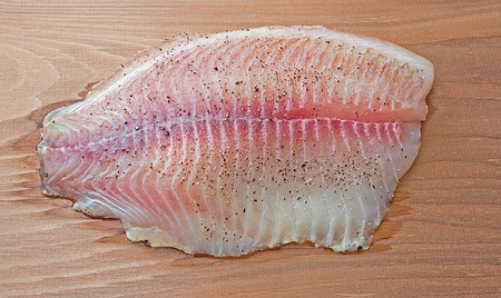 Tilapia being grilled on a cedar plank photo
