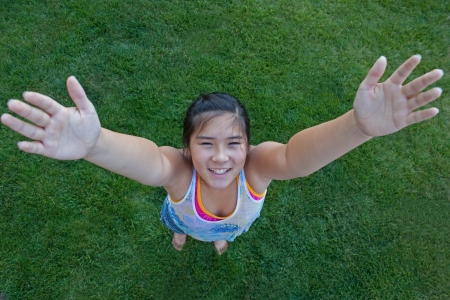 Perspective view of a smiling girl reaching to the sky Foto de archivo