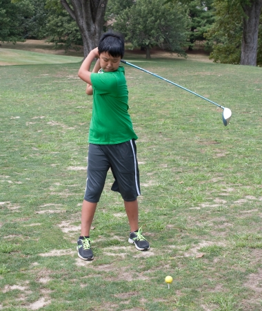 A boy practicing his golf swing at the driving range photo