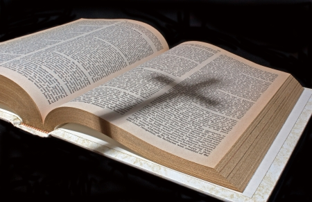 Open Bible with a shadow of a cross photo