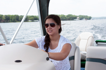 Smiling teen girl driving a boat on the lake