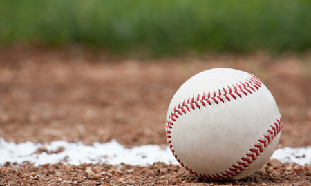 foul: Close-up of a baseball sitting near the foul line