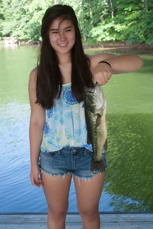 big mouth: Teenage girl smiling and holding a largemouth bass
