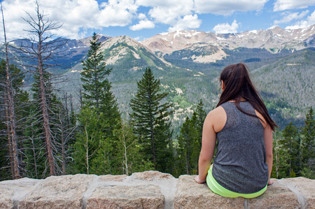Teenage girl sitting on a rock wall looking at the mountains