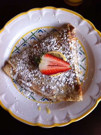 This is a French crepe with powdered sugar. It is filled with lemon curd.