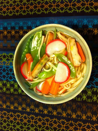 Bowl of udon soup with snow peas and fish cake.