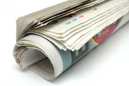 Roll of newspaper on white background photo