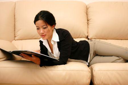 Woman lying on sofa reading photo
