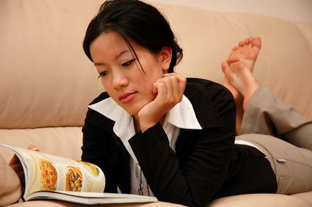 Woman lying on sofa reading Stock Photo