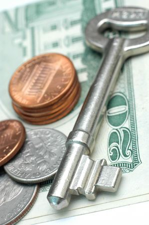Key with US dollar and coins. Low DOF