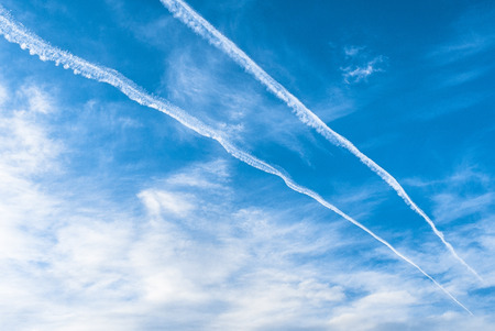 Blue sky, wispy white clouds, and contrails from high flying aircraft