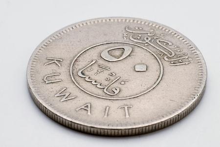 An old sliver Kuwaiti dinar coin macro photograph.