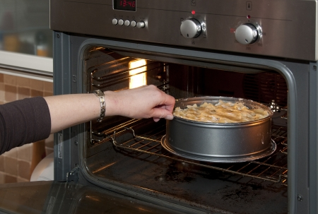 Putting a cake in the oven Stock Photo