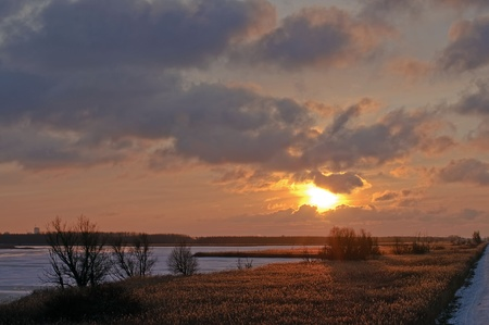 Sunset over reed and a frozen lake photo