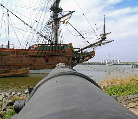 Canon pointed at a historic sailboat, Holland, Europe