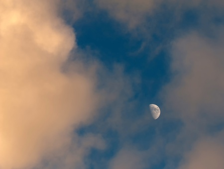 The moon in a blue and cloudy sky