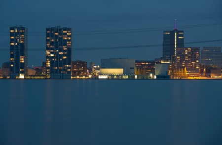 almere: Skyline of a city along a lake at dusk
