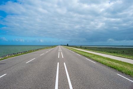dike: Road on a dike along a lake Stock Photo
