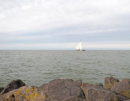 dike: Sailboat sailing along a dike at fall
