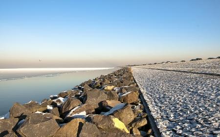 markermeer: Dike along a frozen lake in winter