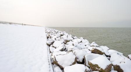 markermeer: Stones covered in snow along a dike in winter