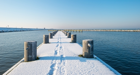 bollard: Jetty covered in snow in winter Stock Photo