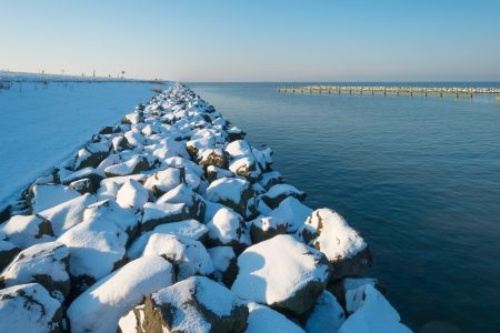 markermeer: Snowy stones protecting a dam along a lake Stock Photo