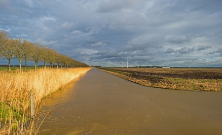 Sunlight and dark clouds over a canal in winter Stock Photo - 17688732