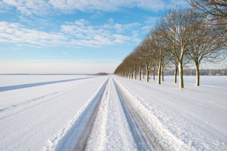 Snowy road through the countryside in sunlight Stockfoto