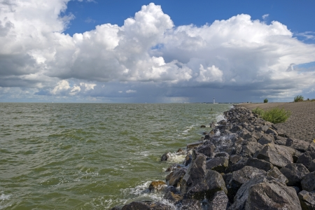 markermeer: Dike protecting a coast under a blue cloudy sky