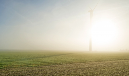 Wind turbine in a hazy sunlit field at fall photo