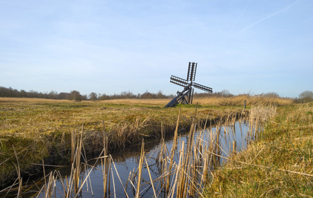 Windmill along a stream through wetland photo