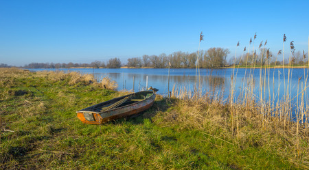 Old rowboat on the shore of a river photo